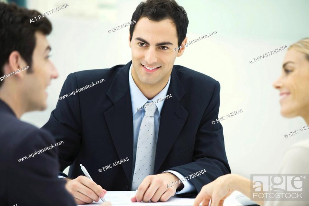 Stock Photo: Business associates having discussion, smiling at each other, man taking notes.
