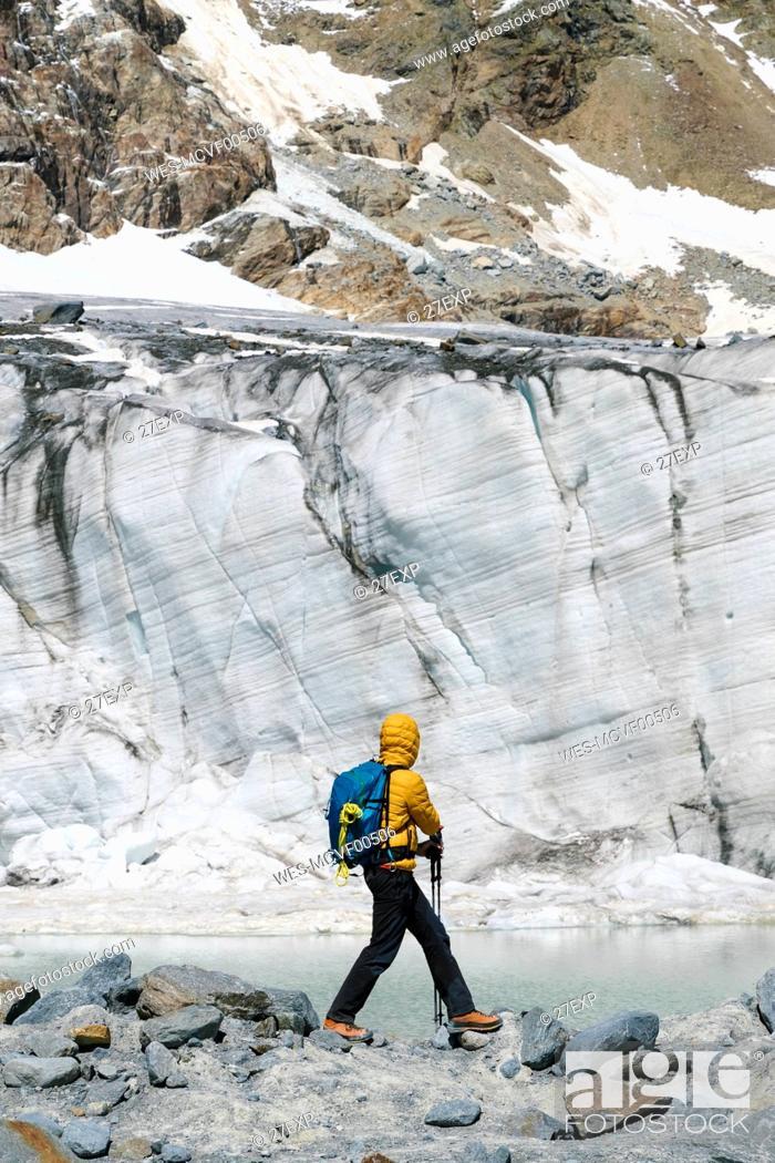 Photo de stock: Mature man exploring melting glacier while standing on rocks.