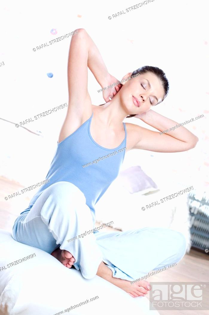 Stock Photo: young woman stretching in bed.