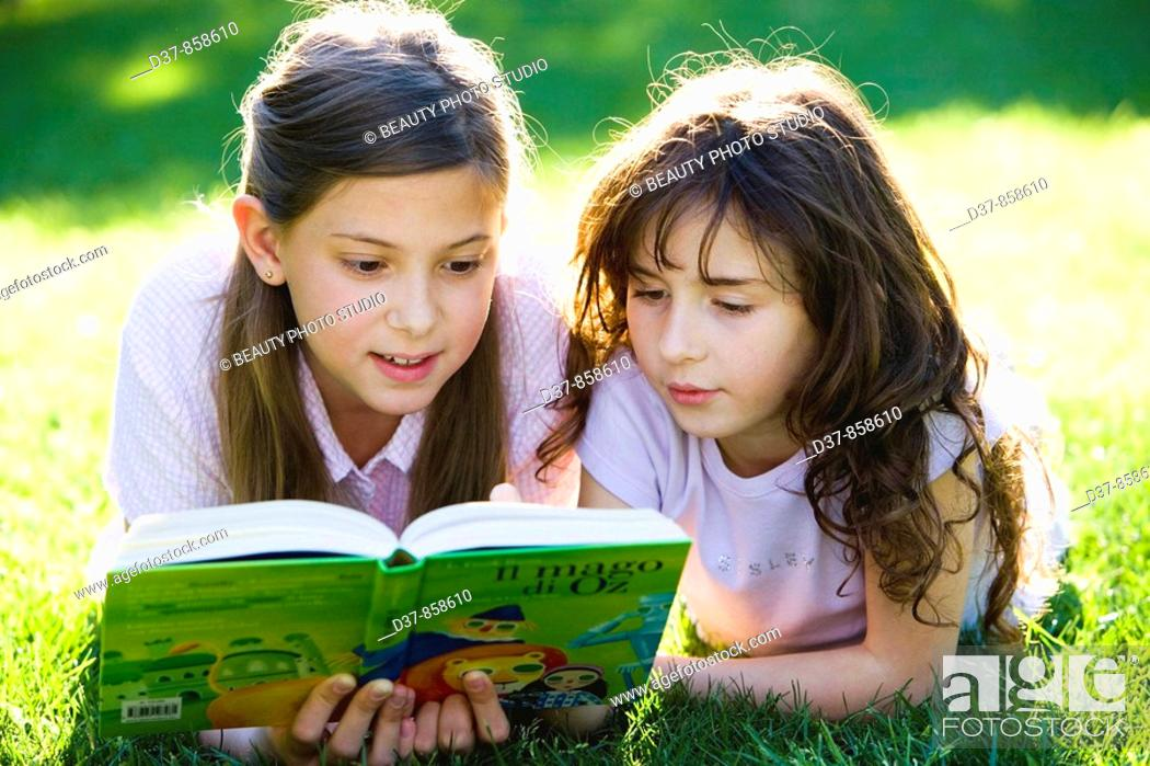 Stock Photo: Two girls reading a book laying on the grass.