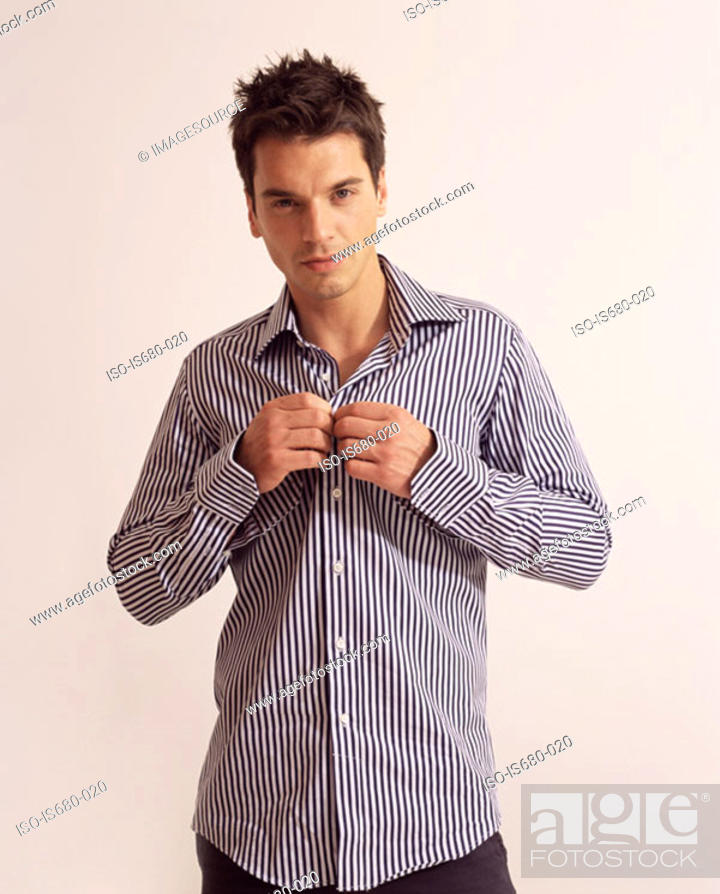Stock Photo: Man putting on a shirt.