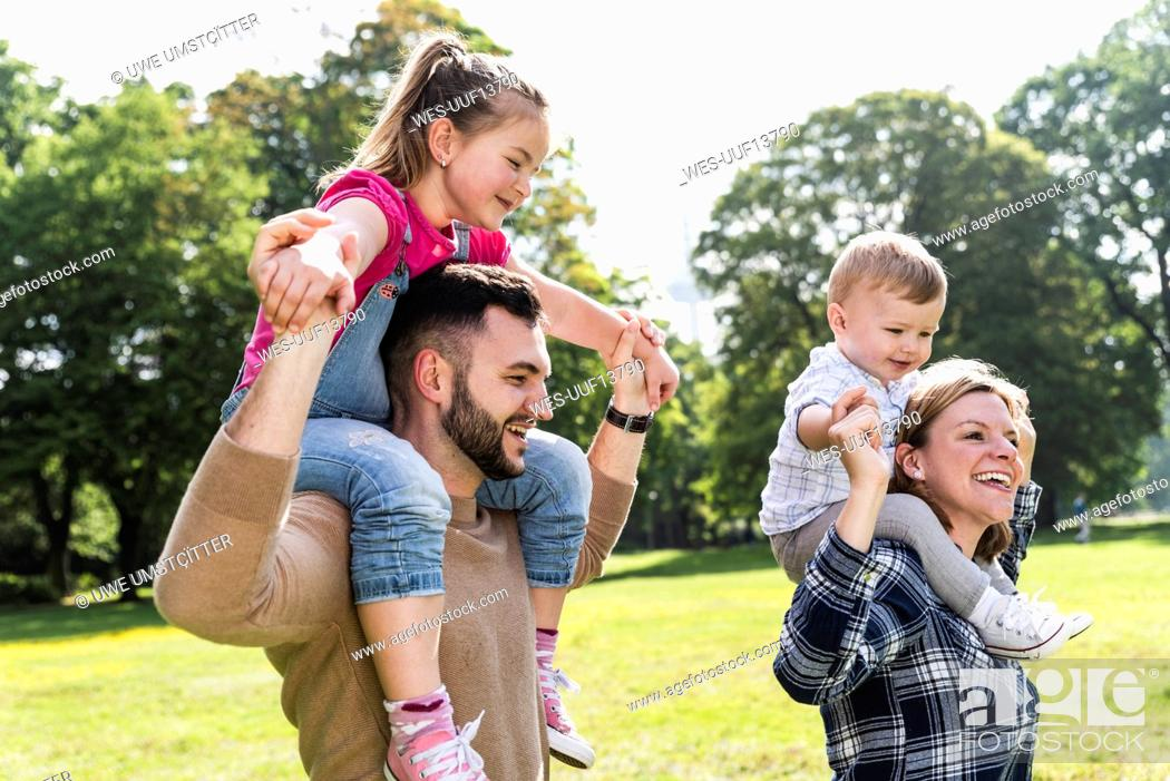 Stock Photo: Happy parents carrying children on shoulders in a park.