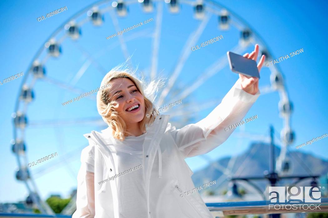 Stock Photo: Woman taking selfie in front of Cape Wheel, Victoria and Alfred Waterfront, Cape Town, South Africa.