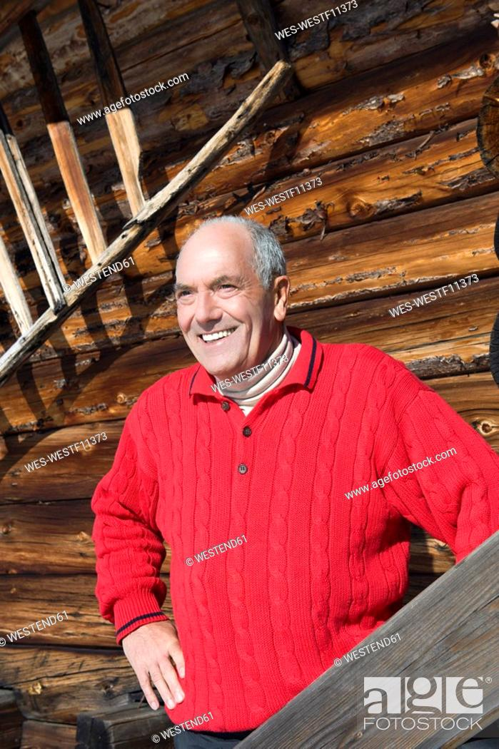 Stock Photo: Italy, South Tyrol, Seiseralm, Senior man standing in front of wooden wall, smiling, portrait.
