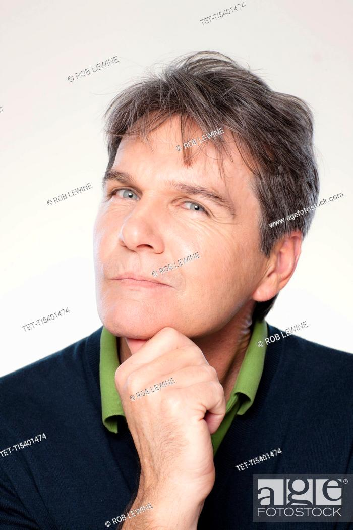 Stock Photo: Studio portrait of mature man with hand on chin.