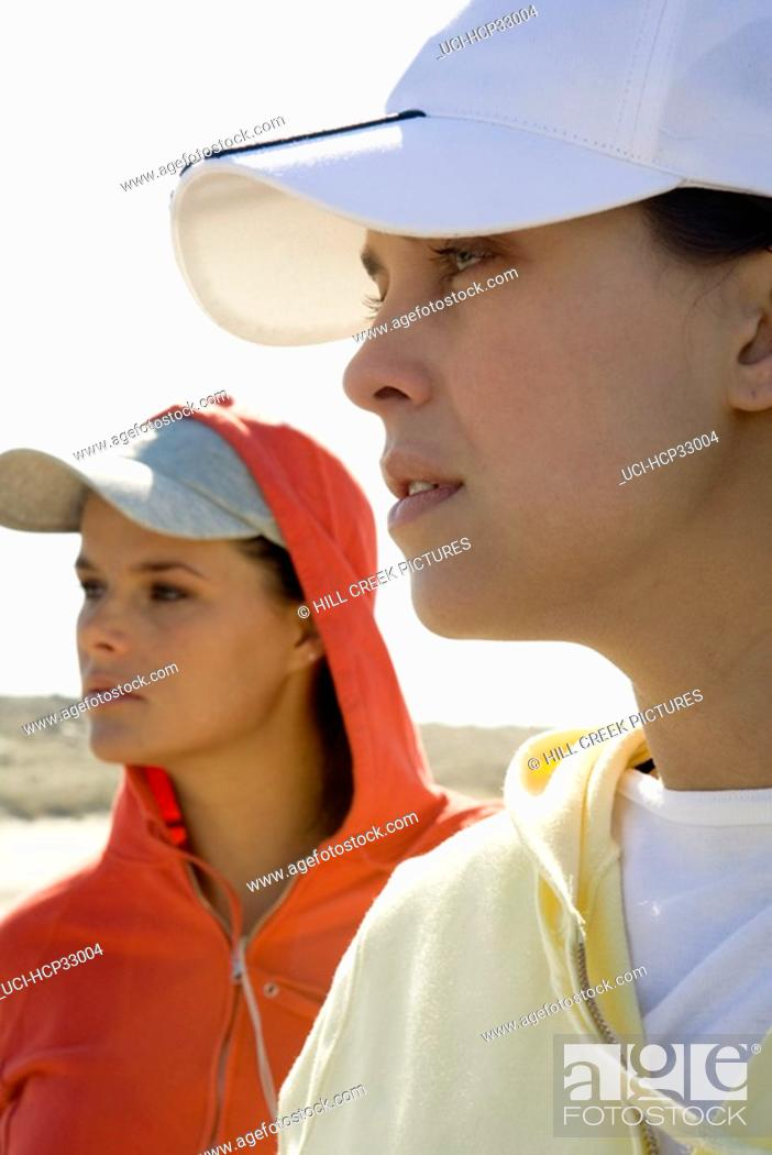 Stock Photo: Side view of young women wearing baseball hats at beach.