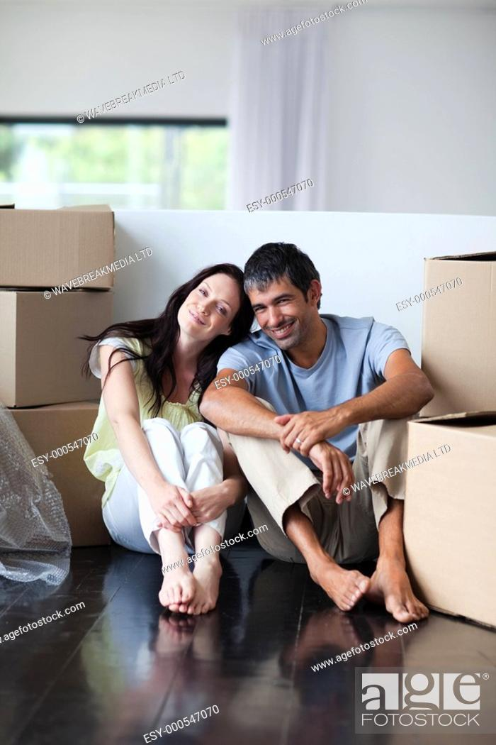Stock Photo: Happy lovers moving house with boxes.