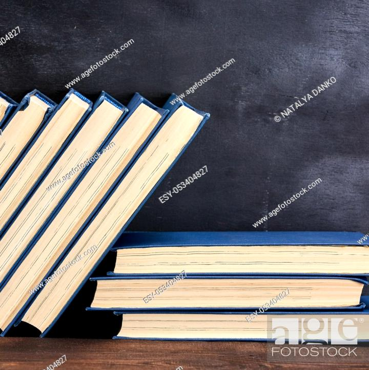 Stock Photo: books in the blue cover, black background, copy space.