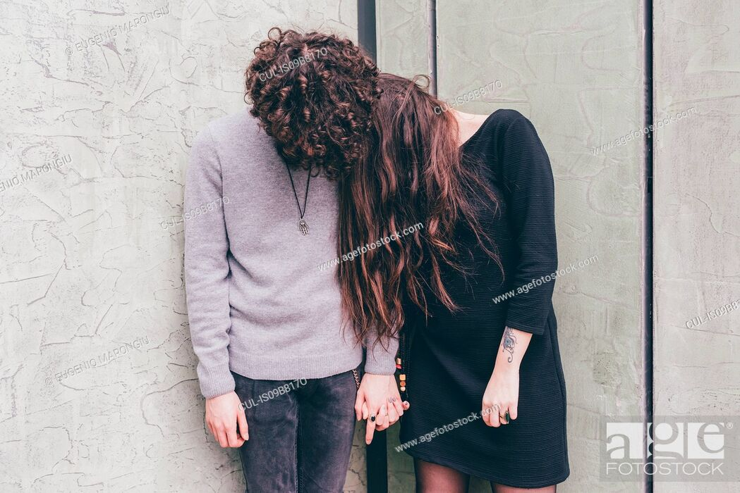 Stock Photo: Young couple outdoors, standing against wall, holding hands, hair covering their faces,.