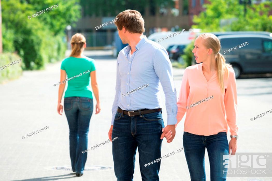 Stock Photo: Young Woman Shouting At Her Boyfriend Looking At Another Woman On Street.