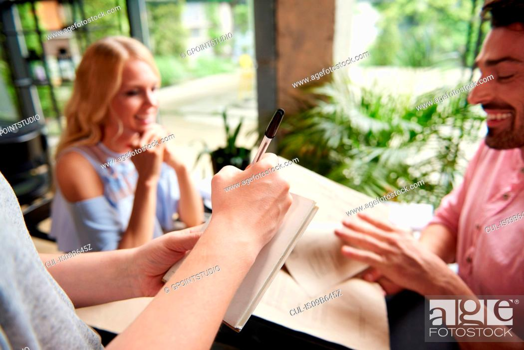 Stock Photo: Over shoulder view of waitress writing order from couple at restaurant table.