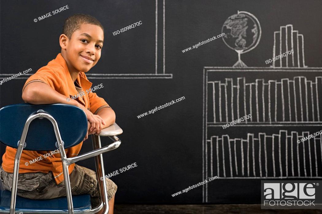Stock Photo: Portrait of a boy sat at a desk.