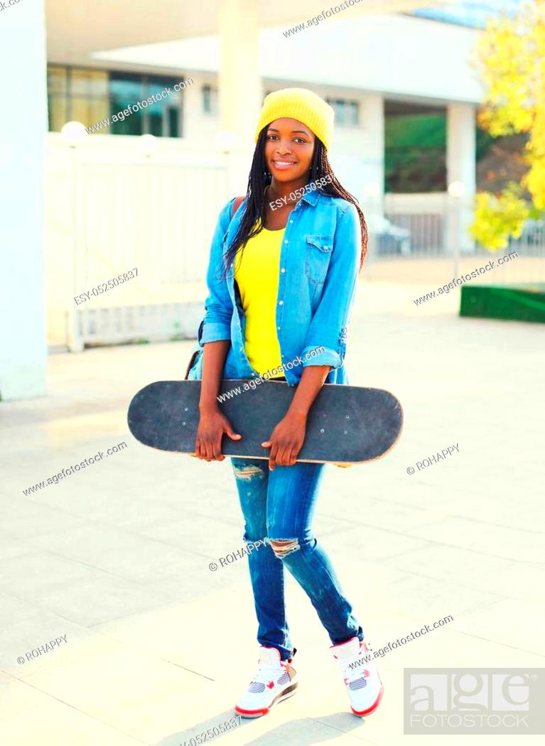 Stock Photo: Fashion young african woman with skateboard in the city.