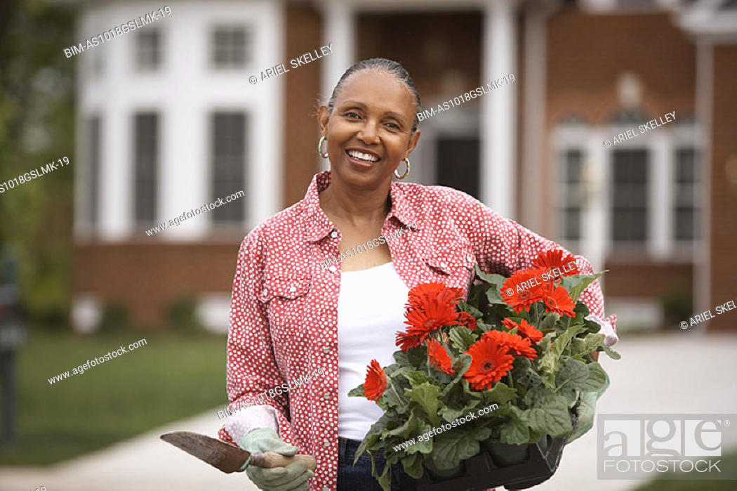 Stock Photo: Woman holding flowering plant.
