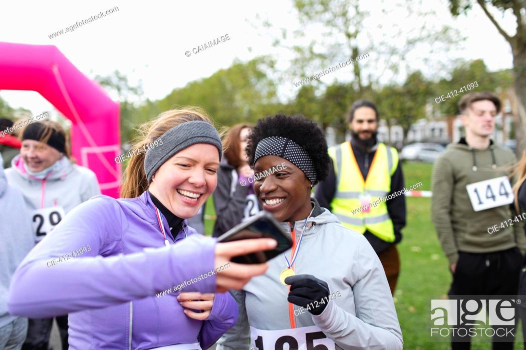 Stock Photo: Female runner friends using smart phone at charity run in park.