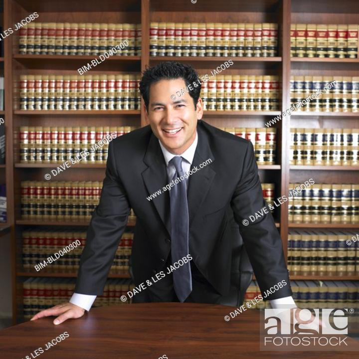 Stock Photo: Mixed Race male lawyer leaning on desk.