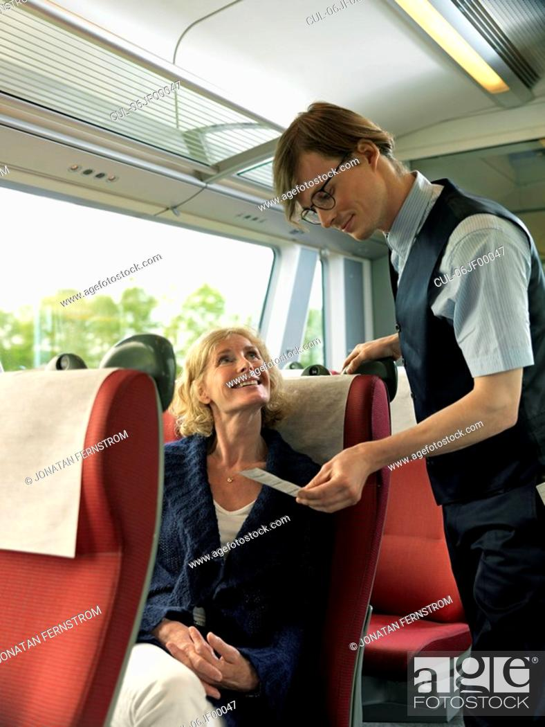 Stock Photo: Woman and conductor on train.