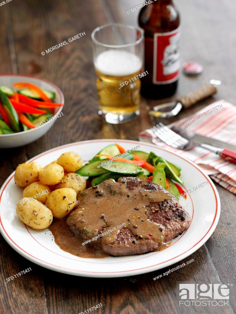 Stock Photo: Peppered steak with roast potatoes and cucumber salad.