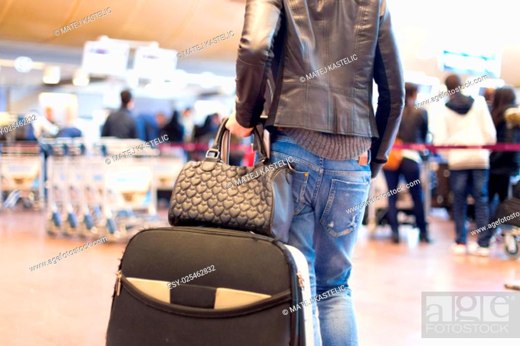 Stock Photo: Casually dressed young stylish female traveller walking the airport terminal hall draging suitcase and a handbag behind her. Blured background.
