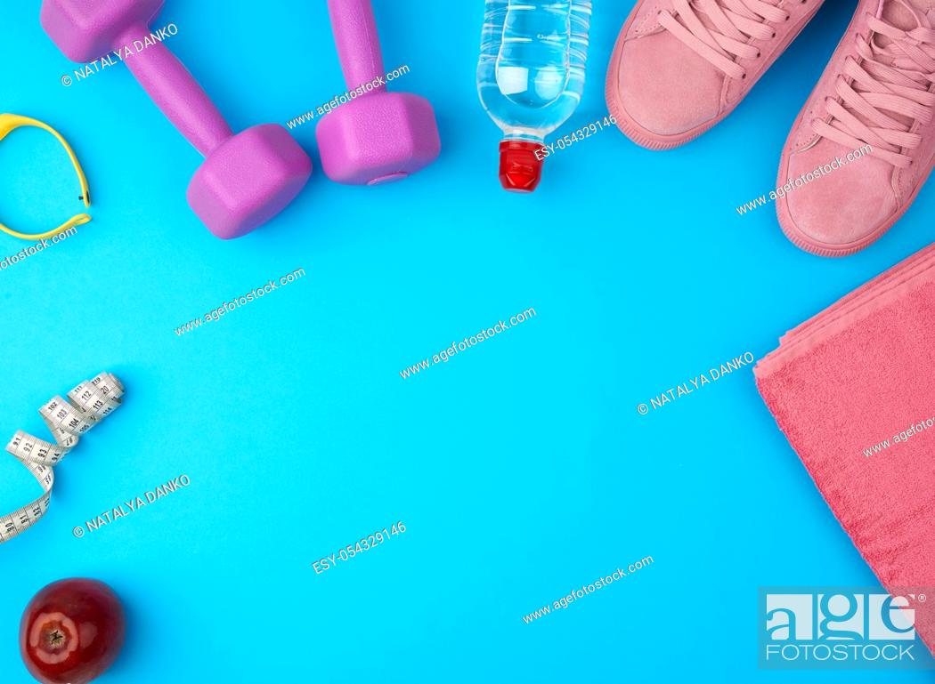 Stock Photo: plastic purple dumbbells, sportswear, water, pink sneakers on a blue background, fitness kit, flat lay, copy space.