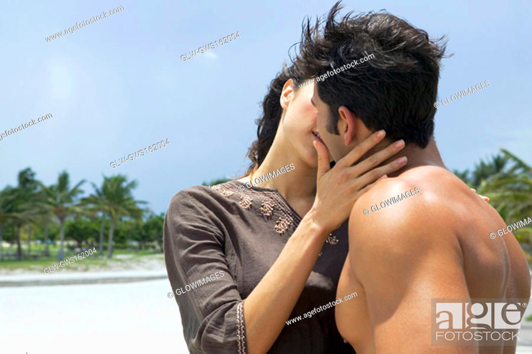 Photo de stock: Close-up of a young woman and a mid adult man kissing each other.