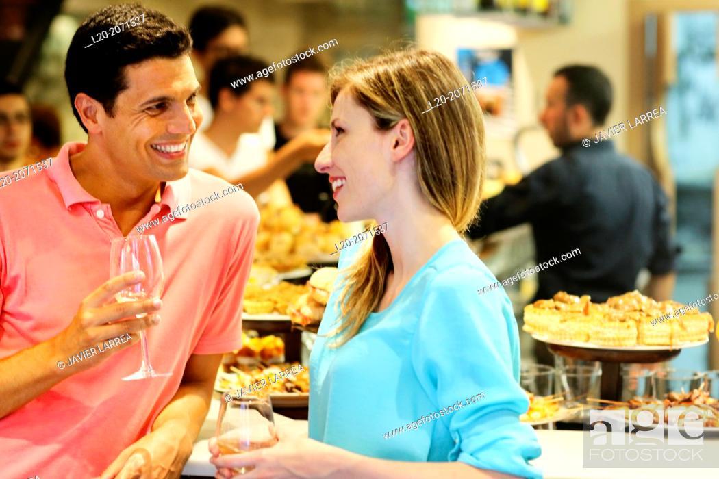 Imagen: Couple drinking wine and eating tapas. Pintxos. Bar txondorra. Parte Vieja. Old town. San Sebastian. Donostia. Gipuzkoa. Basque Country. Spain.