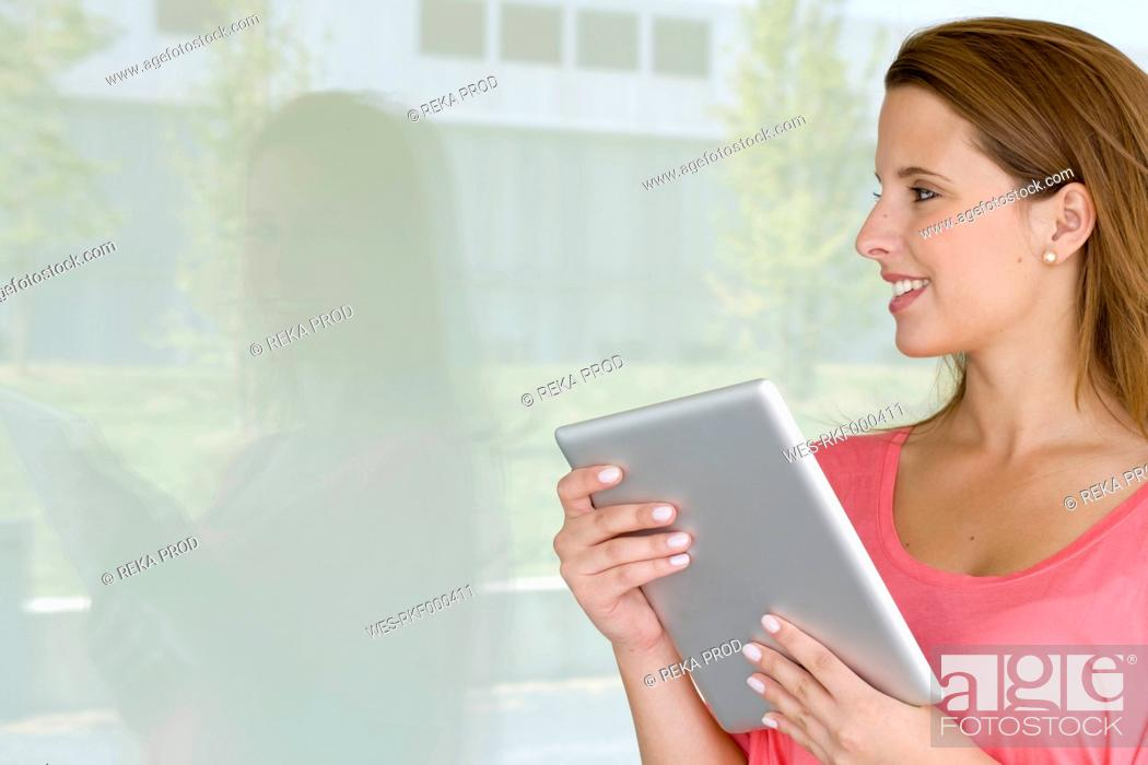 Stock Photo: Europe, Germany, North Rhine Westphalia, Duesseldorf, Young woman with digital tablet, smiling.