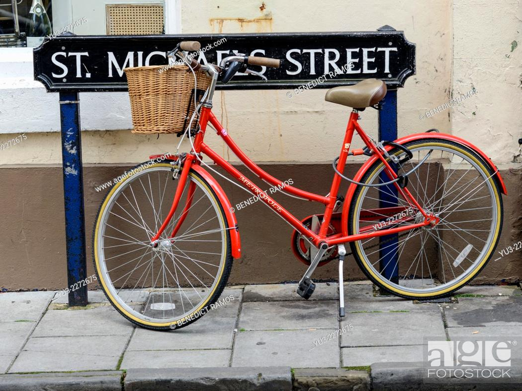 Stock Photo: Red woman's bicycle parked by St Michael's Street road sign, Oxford, England, UK.