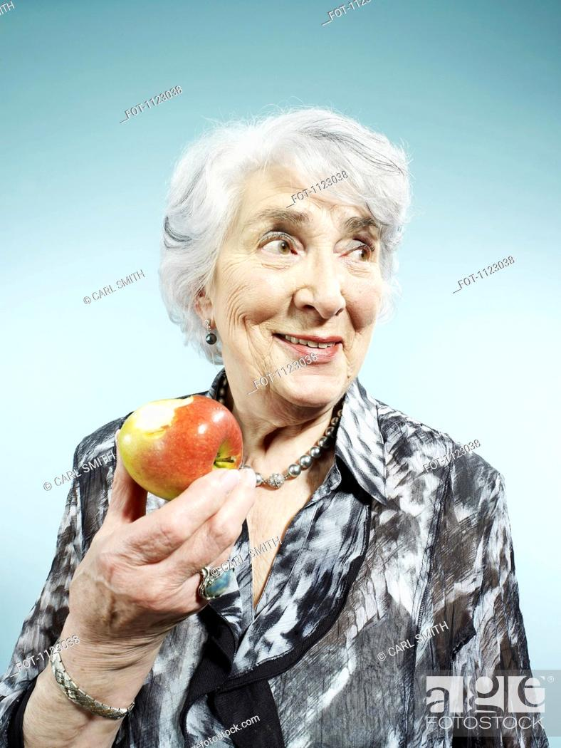 Stock Photo: A senior woman holding an apple with a bite out of it.