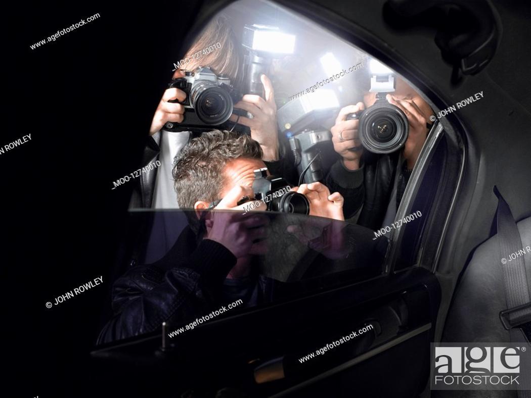 Stock Photo: Paparazzi shooting through car window.