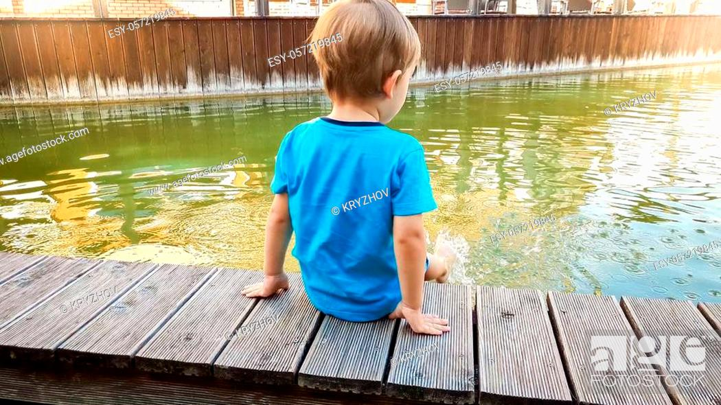 Stock Photo: Image of cute 3 years old little boy sitting on the riverebank at water canal in old town and splashing water with feet.