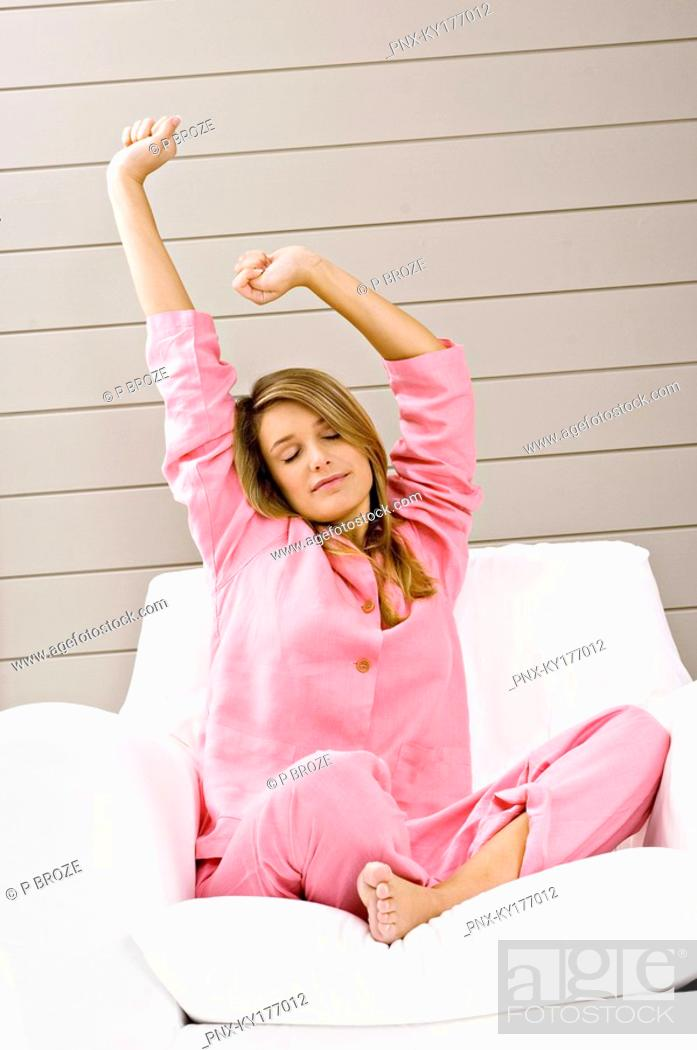 Stock Photo: Young woman sitting in an armchair and stretching her arms.