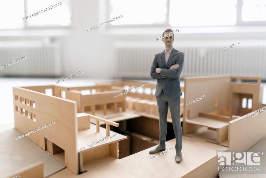 Stock Photo: Miniature businessman figurine standing in architectural model.