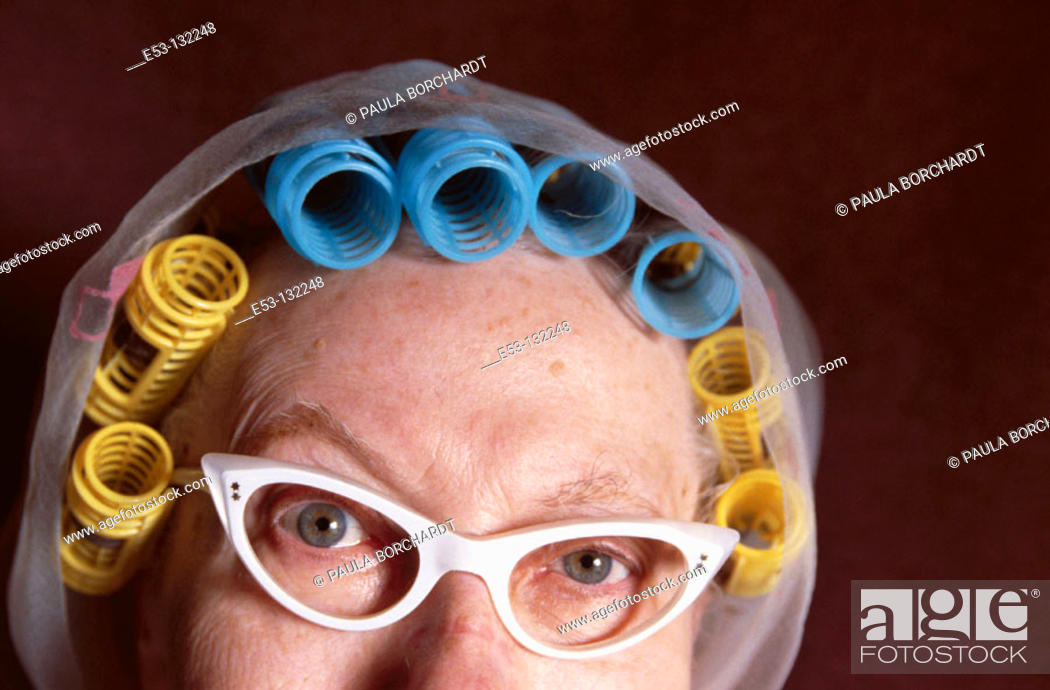 Stock Photo: Senior woman with eyeglasses and hair in curlers.