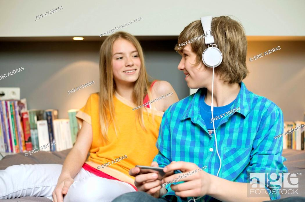 Stock Photo: Teenage boy listening to music on iPod with his sister at home.