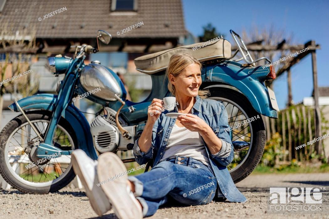 Stock Photo: Smiling woman sitting at vintage motorcycle having a coffee break.