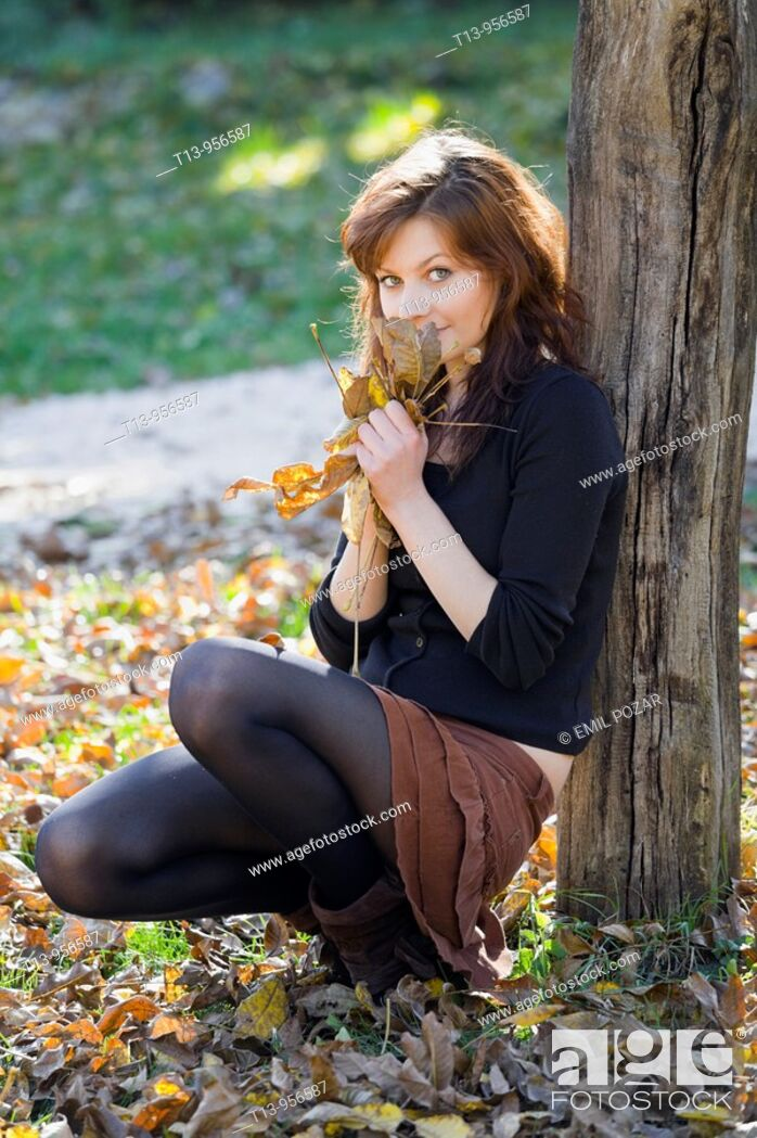 Stock Photo: Hiding behind a bunch of fallen Autumn leaves pretty young woman.