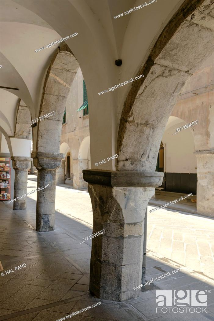 Stock Photo: stone arches and pillars at old medieval covered walkway, shot at Mediterranean little town of Chiavari, Genova, Liguria, Italy.