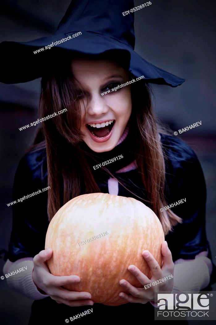 Stock Photo: Portrait of a teenage girl in a witch costume with a pumpkin. Halloween celebration.