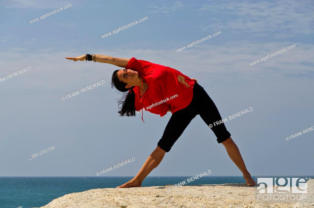 Woman in a yoga position, Trikonasana, by the sea in