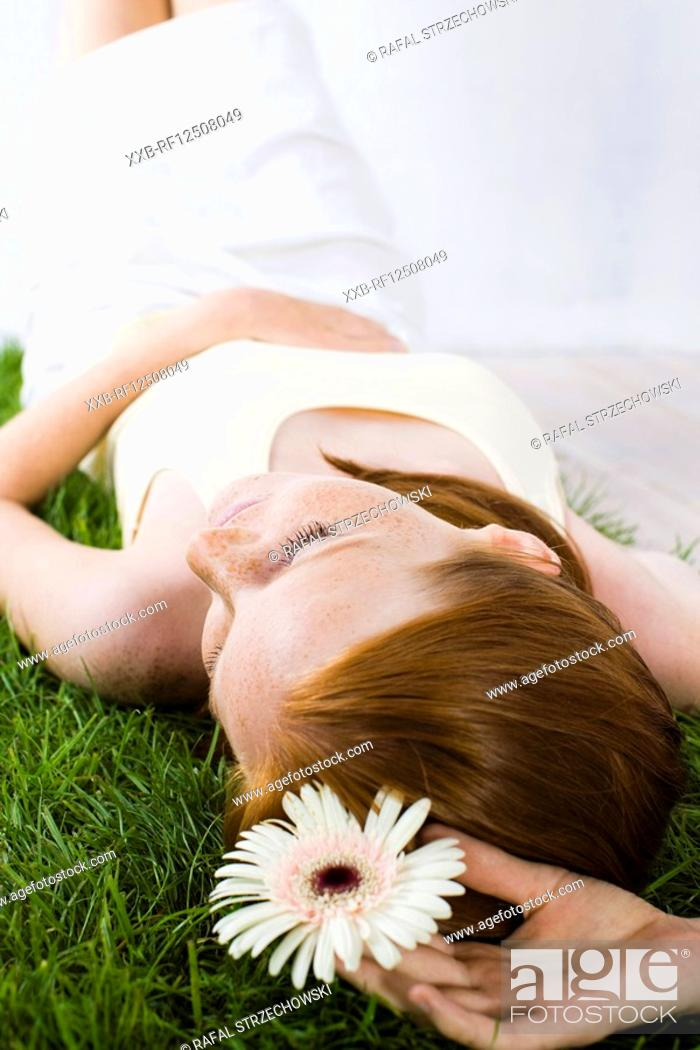 Stock Photo: young woman relaxing on grass.