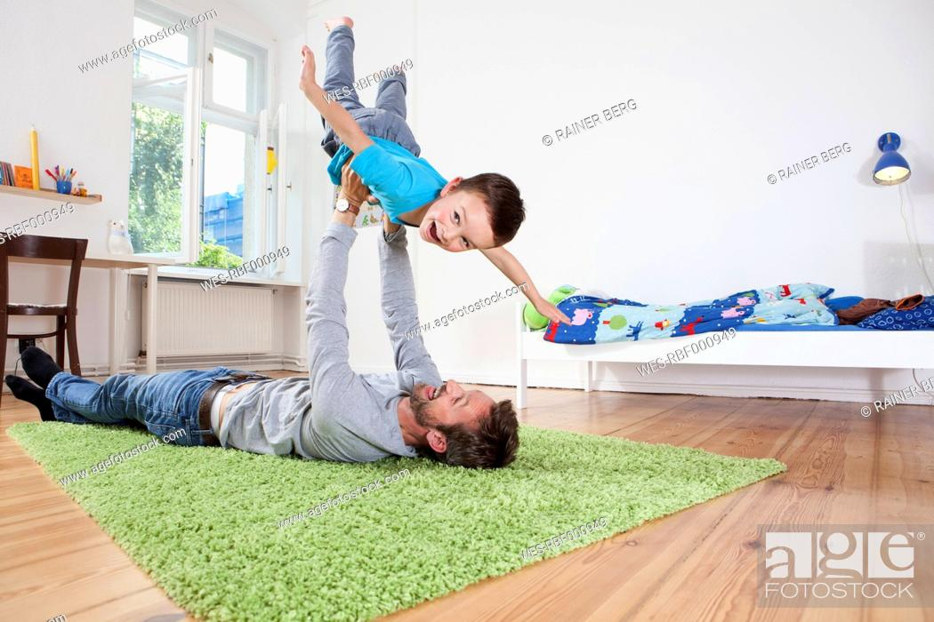 Stock Photo: Germany, Berlin, Father holding son, smiling.