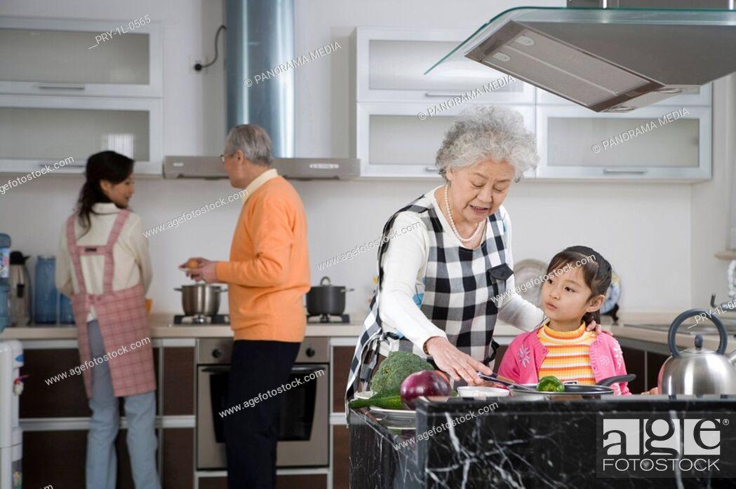 Imagen: Family preparing food in kitchen.