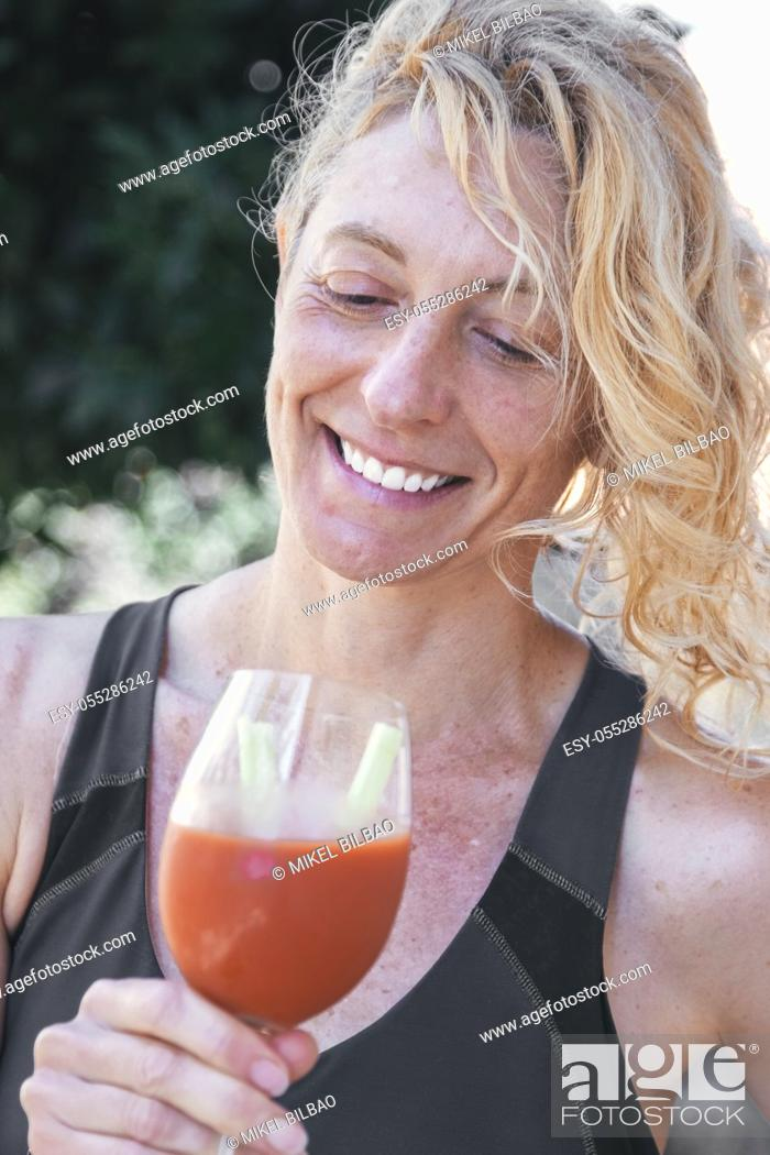 Stock Photo: Young mature blonde woman in sportswear outdoor with a glass of tomato juice.