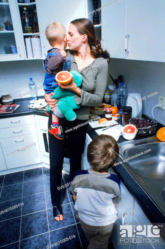 Stock Photo: Mother with her children in the kitchen.