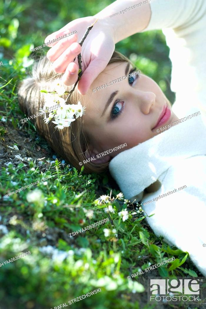 Stock Photo: Teenage girl lying on the ground, holding flowers, smiling at camera.
