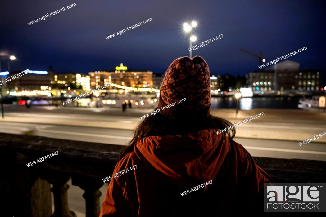 Stock Photo: Back view of woman looking to the city by night.