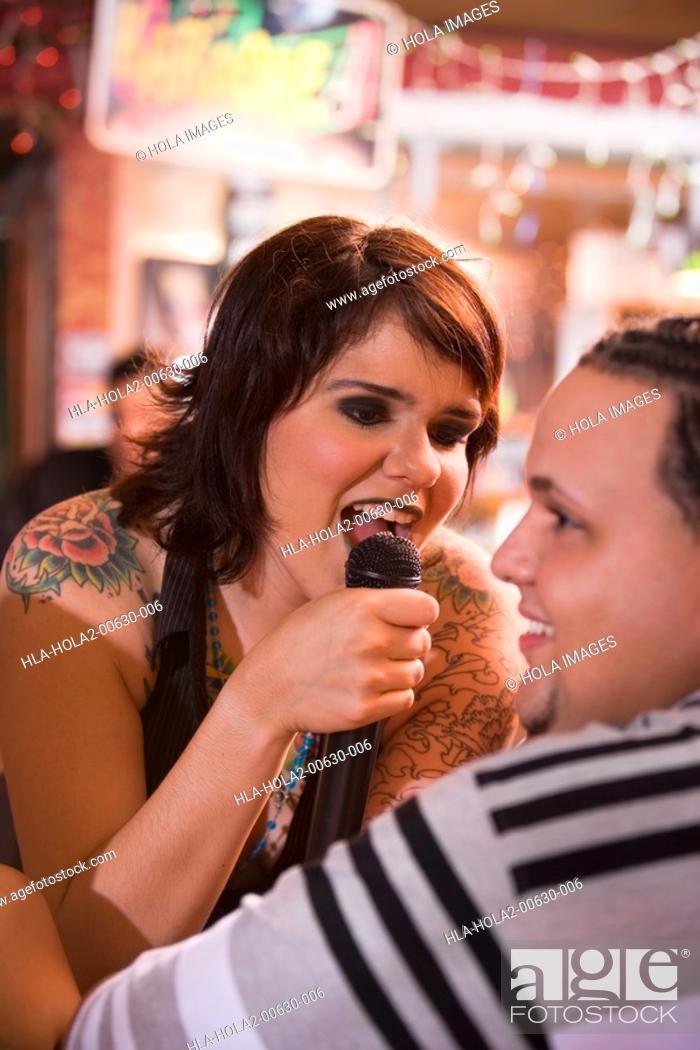 Imagen: Young woman with tatoos singing at bar.