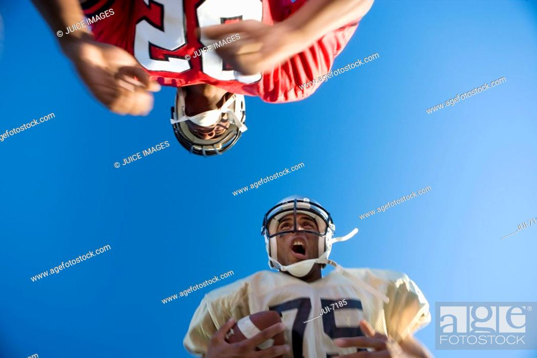 Stock Photo: American football player running with ball at opposing player during competitive game, upward view.