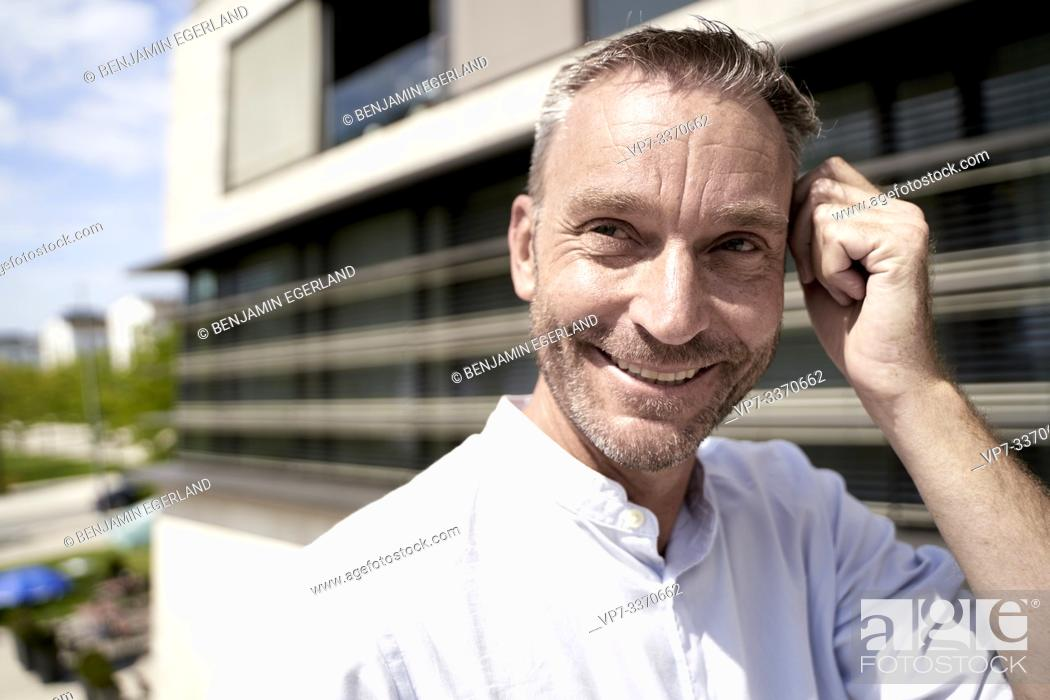 Stock Photo: smiling best ager man in business district.